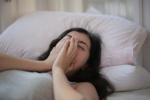 Woman lying on bed covering her face with her hands